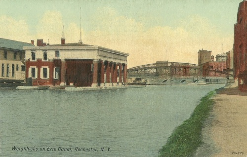 Weighlocks on Erie Canal, Rochester, N.Y. (214976 -- [Leighton & Valentine Co., N.Y.]) - From: Rochester Public Library Local History Division. -- A postcard view of the weighlock, looking north with the city in the background, approximately 1910.