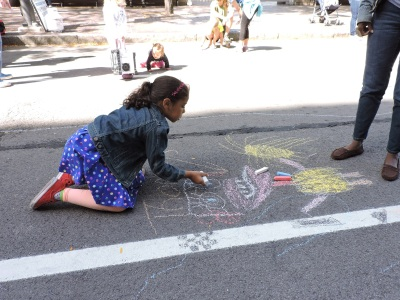Kids from the Carlson MetroCenter YMCA, along with their mentors, decorating the street with chalk art.